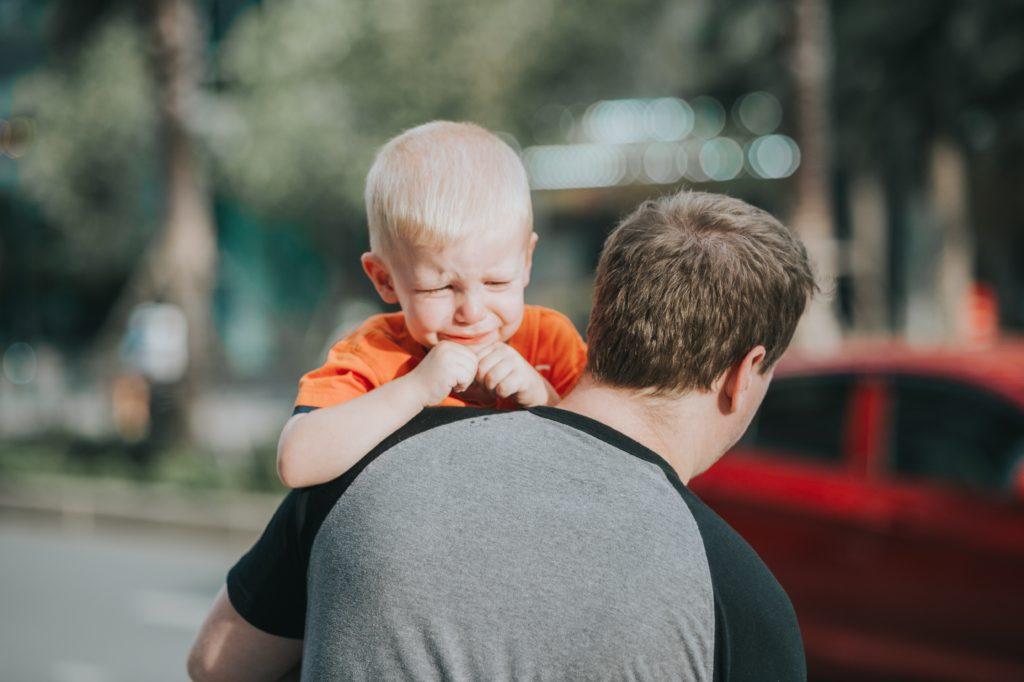 Criança loira chora no colo do pai